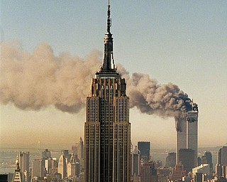 FILE - In this Sept. 11, 2001 file photo, the twin towers of the World Trade Center burn behind the Empire State Building in New York. Osama bin Laden, the glowering mastermind behind the Sept. 11, 2001, terror attacks that killed thousands of Americans, was slain in his luxury hideout in Pakistan early Monday, May 2, 2011 in a firefight with U.S. forces, ending a manhunt that spanned a frustrating decade.