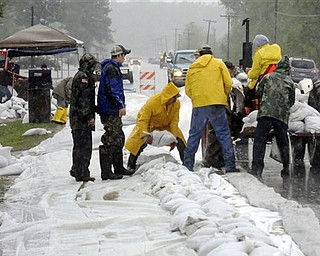 Volunteers hastily work to build a wall of sandbags along Illinois 3 on Sunday, May 1, 2011 in Olive Branch, Ill. Rising floodwaters were only inches from spilling over the opposite side of the highway. Residents hoped the wall would protect homes adjacent to the road, many of which are already surrounded by water on three sides.