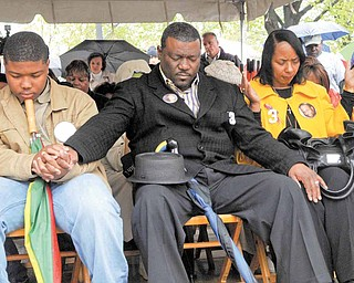 From left, Jamail Johnson's brother, Sidney Hill; step-father, Sidney Hill; and mother, Shirlene Hill, join hands in prayer Tuesday afternoon during a tree-planting ceremony at Youngstown State University. A burr oak tree was planted at the YSU campus core in Johnson's memory. He was shot and killed Feb. 6 while trying to break up a fight at an off-campus party.