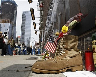 """A pair of military boots, a bottle of whiskey and a memorial candle are placed at the base of a 9-11 memorial across the street from ground zero in New York, Tuesday, May 3, 2011.  The boots and other items were placed there with a sign that reads, """"Today let us pray for peace.""""  Foot traffic has increased at ground zero from tourists and locals alike in the wake of the death of Osama bin Laden in a U.S.-led raid in Pakistan Sunday."""