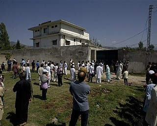 Local people and media gather outside the perimeter wall and sealed gate into the compound and a house where al-Qaida leader Osama bin Laden was caught and killed late Monday, in Abbottabad, Pakistan, on Tuesday, May 3, 2011.  Local residents showed off small parts of what appeared to be a U.S. helicopter that Washington said malfunctioned and was disabled by the American commando strike team as they retreated, while Pakistan's leader on Tuesday denied suggestions that his country's security forces had sheltered Osama bin Laden.