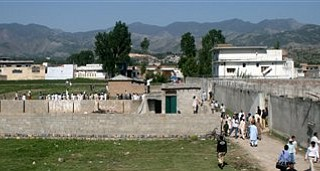 Local people and news media gather round the compound and house, seen on right, of Osama bin Laden as authorities eased the security and allowed people to approach the perimeter of the compound in Abbottabad, Pakistan, on Tuesday, May 3, 2011, after a U.S. military raid late Monday which ended with the death of the al-Qaida leader Osama bin Laden and others inside the compound.  U.S. Navy SEALs swept through the massive compound Monday in pursuit of their target, bin Laden, and it is revealed Tuesday by White House counterterrorism adviser John Brennan that the U.S. already was scouring through items seized in the raid, said to include hard drives, DVD's, a pile of documents and other items.