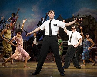 """In this theater publicity image released by Boneau/Bryan-Brown, Andrew Rannells, center, performs with an ensemble cast in """"The Book of Mormon"""" at the Eugene O'Neill Theatre in New York. """"The Book of Mormon"""" nabbed a leading 14 Tony Award nominations Tuesday morning, earning the profane musical nods for best musical, best book of a musical, best original score, two leading actor spots and two featured actor nominations."""
