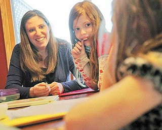 Laurie Thompson, left, is a mother of three and is a surrogate mother of twins for a couple in Spain, the second time she has been a surrogate. Thompson helps her daughters Avery and Kyrra, right, with homework at home in McHenry, Illinois, on April 4, 2011.