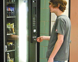 Will Kooyman, a junior at Boardman High School, puts money in one of the school-owned snack vending machines in the cafeteria. Public health and school offi  cials are on a mission to reduce calories and improve nutrition of items sold to students in Mahoning County schools.