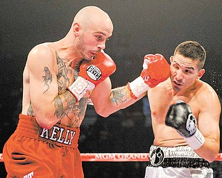 Kelly Pavlik, left, lands a punch against Alfonso Lopez in the first round during a WBO World super bantamweight title bout, Saturday, May 7, 2011, in Las Vegas.