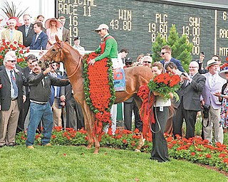 Youngstown businessman Bruce Zoldan (standing behind man holding Animal Kingdom) celebrates with the other owners of the Kentucky Derby winner at Churchill Downs. Behind Zoldan is NBC's Bob Costas.