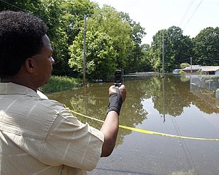 Cedric Briggs takes a photo with his phone in the Box Town neighborhood Sunday, May 8, 2011 in Memphis, Tenn. as flood waters continue to rise along the Mississippi River.