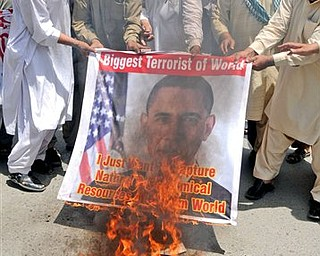 Activists of a local social group Muthahida Shehri Mahaz, burn a banner depicting U.S. President Barack Obama, during a rally to condemn the killing of al-Qaida leader Osama bin Laden, in Multan, Pakistan, Sunday, May 8, 2011.  As U.S. investigators comb through a treasure trove of computer data and documents seized from Osama bin Laden's home, Pakistani officials face a more domestic task: What to do with three of the slain terrorist leader's wives and eight of his children.