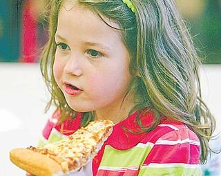 Kindergartner Laura Lanterman enjoys her pizza at the party.