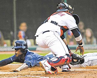 Tampa Bay Rays' B.J. Upton, left, slides safely into home plate as Cleveland Indians catcher Carlos Santana is late with the tag in the fourth inning in a baseball game, Wednesday, May 11, 2011, in Cleveland. Upton scored on a fielders choice by John Jaso.