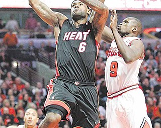 Miami Heat's LeBron James, left, drives to the basket past Chicago Bulls' Luol Deng during the first quarter in Game 1 of the NBA Eastern Conference Finals basketball series  Sunday, May 15, 2011 in Chicago.