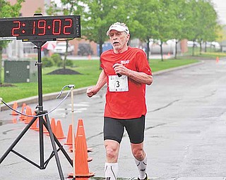 Dave White, 70, crosses the finish line as the oldest competitor at the  2011 Davis Family YMCA/ Steel Valley Tri Club Spring Distance Triathalon.