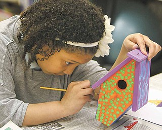 Jaylyn Graves, a student at Mollie Kessler School in Youngstown, concentrates as she paints her birdhouse. Students at the school studied homelessness. The birdhouses will go to Habitat for Humanity.