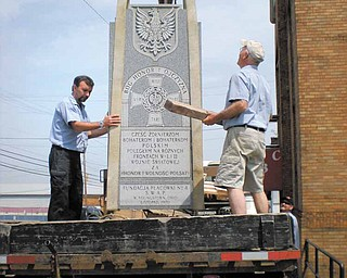 Workers from O.T. Beight & Sons Inc. monument company of Boardman load a monument to Polish veterans of World Wars I and II onto a truck last week after removing it from the front of the vacant former Krakusy Hall in Youngstown. The monument will be rededicated June 25 in Peterson Park in Poland.