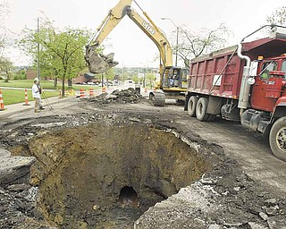 Youngstown Street Department workers remove debris from a sinkhole on Belmont Avenue. An aged sewer line collapsed, causing the ground to erode beneath the North Side street. The collapse took place either late Sunday night or early Monday.