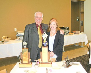 Past District Governor Bill Johnson and Susan Leetch, president of the Rotary Club of Austintown., view the awards presented to the club for its year of service at a recent District 6650 conference in Canton.