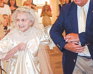 In this May 10, 2011 photo provided by Kristi Fulton, Agnes Anderson, 98, of Laketon Township is escorted by her son, Dick Anderson, down the aisle of Samuel Lutheran Church, in Muskegon, Mich., during a vintage bridal gown fashion show. Anderson wore the dress in 1938 when she married her college sweetheart, Delmar Anderson, a union that lasted more than 50 years until Delmar's death in 1989.
