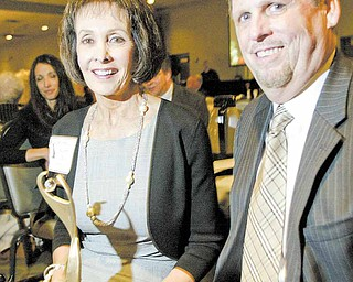Martha Bushey, with her husband Michael at her side, proudly holds the Athena award. Bushey was named the 2011 Athena winner during a banquet Thursday at Mr. Anthony's in Boardman. The event is hosted by the Youngstown/Warren Regional Chamber and The Vindicator.