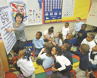 """Marie Economos of Community Solutions, Warren, recites the """"Cooperation Poem"""" with kindergarten students at Taft Elementary School, Youngstown. The kindergartners participated in Project KIND through Community Solutions, which is funded by Youngstown schools, the Raymond John Wean Foundation and the Youngstown Foundation. The program, which ran for 12 weeks at the school, focuses on good  behavior and positive character traits."""