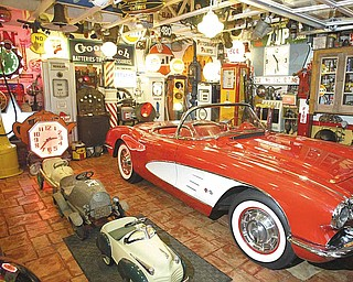 Inside the station is a 1959 Chevrolet Corvette, which is surrounded by historic gas pumps and other car-related memorabilia, including traffic lights and a motor-ignition tester.