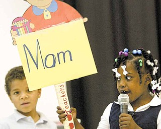 Jevonta Predergast, from left, and Ne'Ahra Page, kindergarten students at Williamson Elementary School in Youngstown, sing during a tribute to mothers Monday at the school.