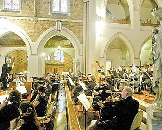 Conductor Michael David Gelfand, a music professor at YSU, leads the Youngstown Symphony Orchestra on Tuesday during a concert marking the 100th anniversary of St. Patrick Church in Youngstown.