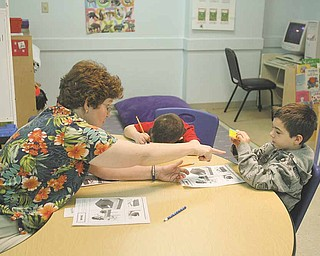 Ann Ferguson helps Brendan Baird and Justin Clark with a visual exercise at The Potential Development Center, designed to give easily distracted autistic children a structured environment.