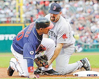 Boston Red Sox third baseman Kevin Youkilis, right, tags out Cleveland Indians' Orlando Cabrera at third base in the second inning of a baseball game Tuesday, May 24, 2011, in Cleveland. Cabrera tried to advance from first on an RBI single by Ezequiel Carrera.