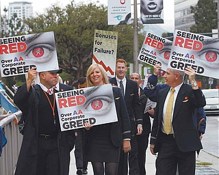 In this May 18, 2011 file photo, American Americans pilots, flight attendants and others picket outside the annual shareholders meeting of AMR Corp., parent company of the airline, outside the Hyatt Regency Century Plaza Hotel in Los Angeles. When it's time for the annual meeting and things might get ugly, there's no place like the road.