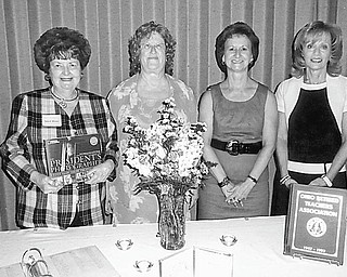 """Remembering teachers: At its annual In-Memoriam and Remembrance Service, the Mahoning Retired Teachers Association eulogized deceased teachers from Mahoning County. During the service, Sally Winsen, at left, presented to Linda Vuletich, MRTA president, standing next to her, this year's memorial book by John Bredar, titled """"The President's Photographer."""" The book will become part of the permanent collection of the Youngstown Public Library on behalf of the John M. Knapick Memorial for deceased MRTA members. Continuing from left to right are Martha Lopez, Remembrance chairwoman, and Joan Sonnett, Remembrance committee member."""