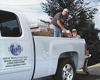 Dealership deliverance: Jim Contant, left, and Jim Lawrence, of First Federated Church of North Jackson, unload the first packages of food delivered by Spitzer Chevrolet from Second Harvest Food Bank. More than 1,000 pounds of food are off-loaded by volunteers. Spitzer Chevrolet, across the street from the church, on Mahoning Avenue, is donating the vehicle and driver twice a month to help the church feed the hungry.