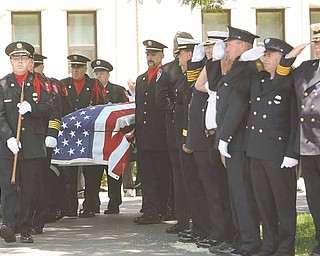 Fellow firefighters from the Mahoning Valley salute the coffin of Cardinal Joint Fire District Chief Robert Tieche as it is carried out of Canfield Methodist Church. Tieche was buried Thursday at Canfield Village Cemetery, five days after he died.