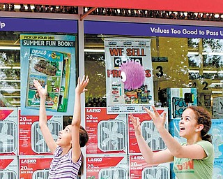 In this photo taken May 29, 2011,  young girls play as they pass a Harlem Deal$ store in New York, where a six-ounce New York strip steak can be purchased for $1.50.  Deal$ stores are owned by Dollar Tree, which sells a variety of items for $1. As May came to a close, the company said it continues to see more customers who are spending more per visit.  Dollar stores pose the biggest threat Wal-Mart, the nation's biggest retailer. (AP Photo/Kathy Willens)