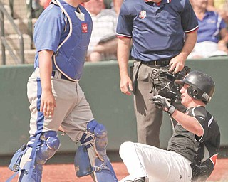 Delphos St. John catcher Austin Reindel watches as Springfield's Brad Ferraro slides safely into home plate during their Division IV baseball semifinal Thursday in Huntington Park. The Tigers defeated the Blue Jays, 9-2, to  advance to the state final Saturday against Minster.