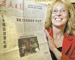 Louise Mason, principal of Girard Junior High School, holds up a Chinese newspaper with a photo and story on China Exchange Initiative, which arranges for American and Chinese educators to spend time in one another's countries. She was on a trip to China from April 6 to 24.