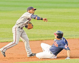 Minnesota Twins shortstop Alexi Casilla throws to first base after getting Cleveland Indians' Asdrubal Cabrera out at second base in the first inning in a baseball game, Tuesday, June 7, 2011, in Cleveland. Carlos Santana was out at first base for the double play. The Indians won 1-0. (AP Photo/Tony Dejak)