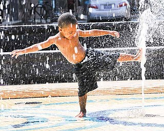 Damien Sheffield, 2, plays in a water fountain in Washington, Wednesday, June 8, 2011. The official start of summer is still two weeks away, but much of the nation is sweating through near-record temperatures, with heat advisories and warnings issued across the Northeast, mid-Atlantic and upper Midwest. (AP Photo/Alex Brandon)