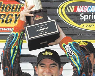 Jeff Gordon poses with the trophy in victory lane after winning the NASCAR Sprint Cup Series auto race, Sunday, June 12, 2011, in Long Pond, Pa. (AP Photo/Russ Hamilton Sr.)