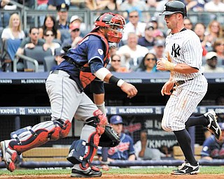 New York Yankees' Brett Gardner, right, runs past Cleveland Indians catcher Carlos Santana to score on a sacrifice fly by Curtis Granderson in the third inning of a baseball game on Sunday, June 12, 2011, in New York. (AP Photo/Kathy Kmonicek)
