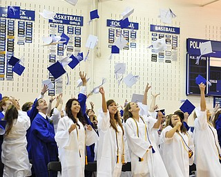 Poland High School seniors throw their caps in the air after graduating Sunday afternoon.