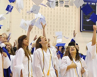 Poland High School seniors Danielle Mullis, Lidia Mowad, Sarah Lankitus throw their caps in the air after graduating.