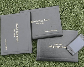ROBERT  K.  YOSAY  | THE VINDICATOR --..Sign of the times as diplomas and an IPHONE lay on the turf..Canfield High School 2011 graduation at the Stadium - .. -30-..(AP Photo/The Vindicator, Robert K. Yosay)