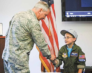 "Cameron receives congratulations from by Air Force Reserve Col. Stephen J. ""Fritz"" Linsenmeyer, commander of the 910th and the Youngstown Air Reserve Station in Vienna. The Pilot for a Day program provides a day of activities at the 910th to children who live with a chronic or life-threatening disease or illness."