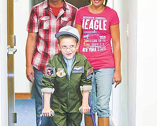 Cameron Shull, sworn in Wednesday as an honorary Air Force Reserve 2nd Lieutenant as part of the 910th Airlift Wing's Pilot for a Day program, is shown at the 910th headquarters building at the Youngstown Air Reserve Station in Vienna with his parents, Michael Merten and Kim Shull. Cameron has cerebral palsy.