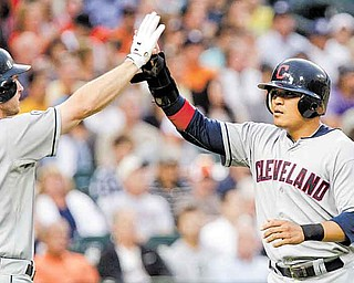Cleveland Indians' Shin-Soo Choo, right, is congratulated at home plate by teammate Lou Marson after scoring from second base on a hit by Orlando Cabrera during the fourth inning of a baseball game against the Detroit Tigers in Detroit, Wednesday, June 15, 2011. (AP Photo/Carlos Osorio)