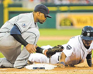 Detroit Tigers' Ramon Santiago, right, makes it safely back to first base and beats the tag from Cleveland Indians first baseman Carlos Santana during the fourth inning of a baseball game in Detroit, Wednesday, June 15, 2011. (AP Photo/Carlos Osorio)