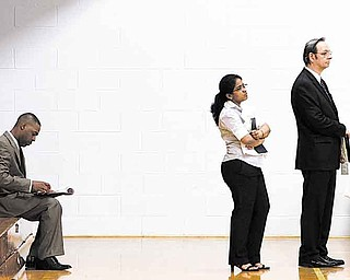Job seekers wait in a line at a job fair in Southfield, Mich., Wednesday, June 15, 2011. Fewer Americans applied for unemployment benefits last week, though the number of applications remains above levels consistent with a healthy economy.  (AP Photo/Paul Sancya)