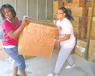 Juliana Yasnowski, left, founder of All About Children's Needs Inc., loads a box into a container bound for Africa with help from Jessica Hancock. Boxes of donations for impoverished African children were loaded into a 40-foot container earlier this month at Uncle Bob's Self-Storage in Hermitage. Donations are still being sought for the relief program.