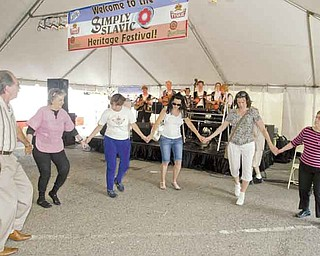Taking part in a traditional Slavic dance to Tamburitza music are, from left, George Metzka, Libby Fil, Janine Mentzer, Lisa Nagy and Paula Horvath Festival attendees had a chance to dance to several Slavic-style bands.